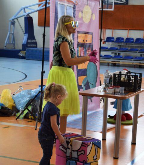 kobieta w żółtej spódnicy stoi przy stoliku, obok mała dziewczynka