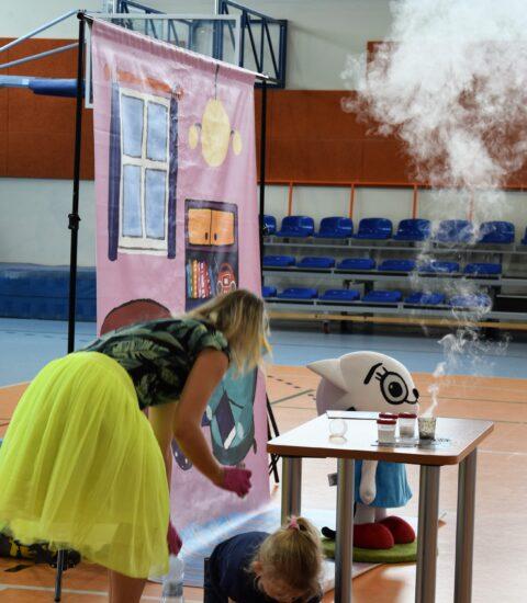 kobieta w żółtej spódnicy pochyla się nad stolikiem, nad którym unosi się dym