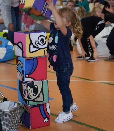 mała dziewczynka układa duże kolorowe klocki