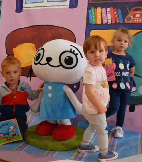 chłopiec trzymający książkę, duża maskatka Kici Koci i dwie dziewczynki na tle ścianki imitującej pokój