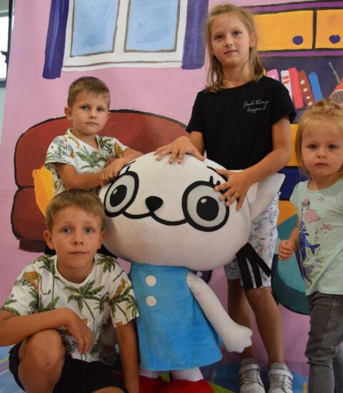 grupka dzieci stoją obok dużej maskotki kotki