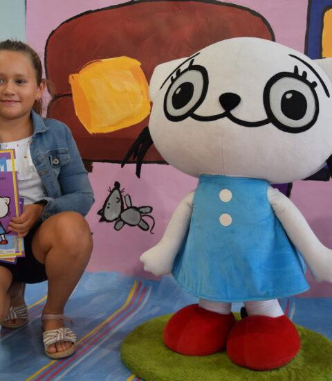 dziewczynka kuca obok dużej maskotki kotki, w rękach trzyma książkę