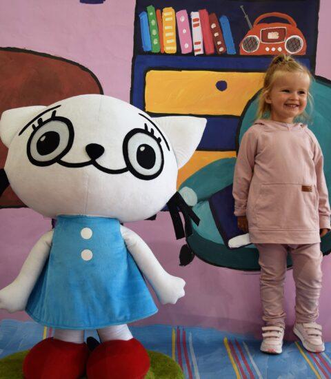 mała dziewczynka stoi obok dużej maskotki kotki