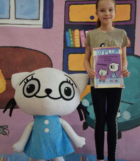 dziewczynka stoi obok dużej maskotki kotki, w rękach trzyma książkę