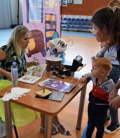 kobieta siedzi przy stole, w ręku trzyma otwartą książkę, naprzeciwko kobieta z małym chłopcem