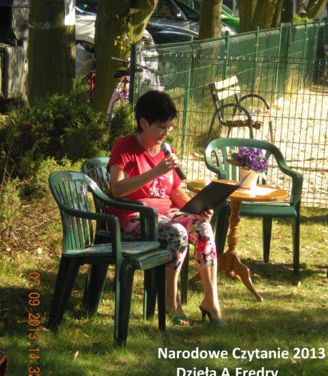 kobieta w czerwonej bluzce siedzi na krześle, mówi do mikrofonu