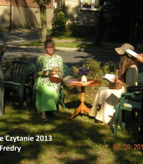 dwie dziewczyny siedzą na krzesłach wśród drzew, obok nich stoi dziewczyna w długiej sukni i chłopak w czarnym kapeluszu