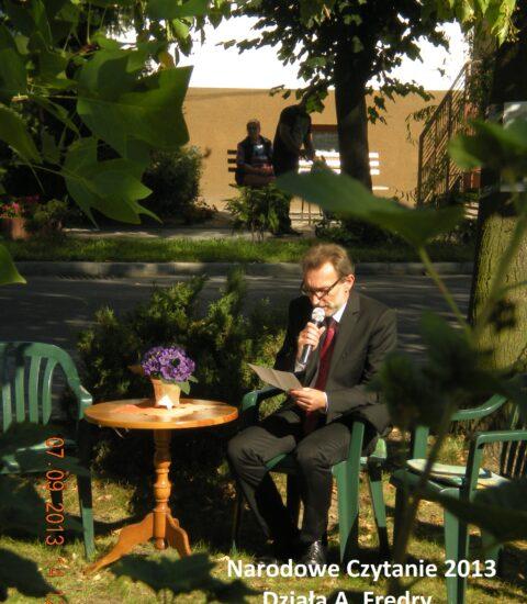 mężczyzna siedzi wśród drzew, mówi do mikrofonu