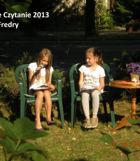 dwie dziewczynki siedzące na krzesłach wśród drzew, jedna trzyma mikrofon