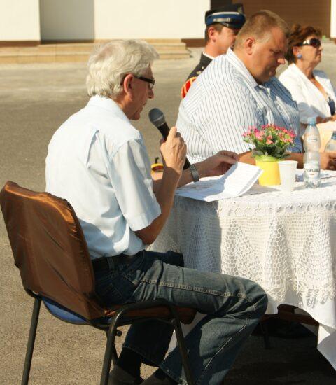 na pierwszym planie mężczyzna siedzi na krześle tyłem, w ręku trzyma mikrofon