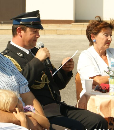 mężczyzna stroju strażaka siedzi na krześle, w ręku trzyma mikrofon, obok siedzi kobieta