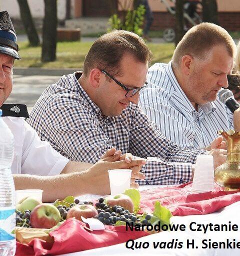 trzech mężczyzn i kobieta siedzą obok siebie przy stole, jeden z nich trzyma w ręku mikrofon