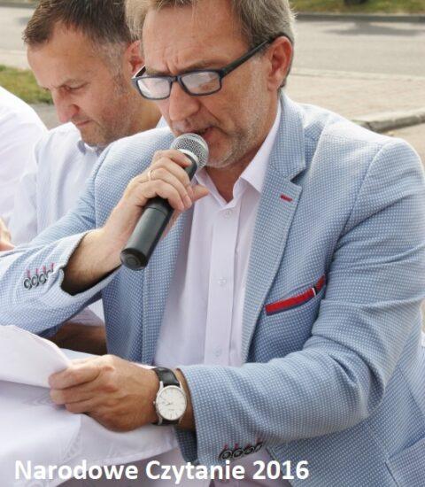 mężczyzna w jasnej marynarce siedzi przy stole czyta do mikrofonu