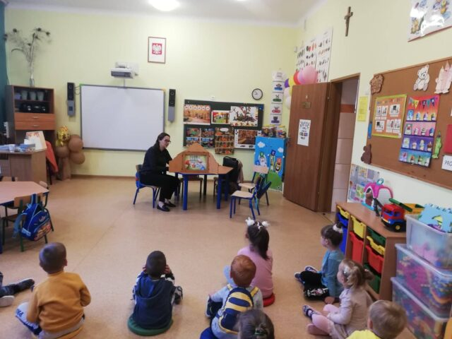grupa dzieci siedzących na podłodze, w oddali kobieta przy stoliku czyta bajkę