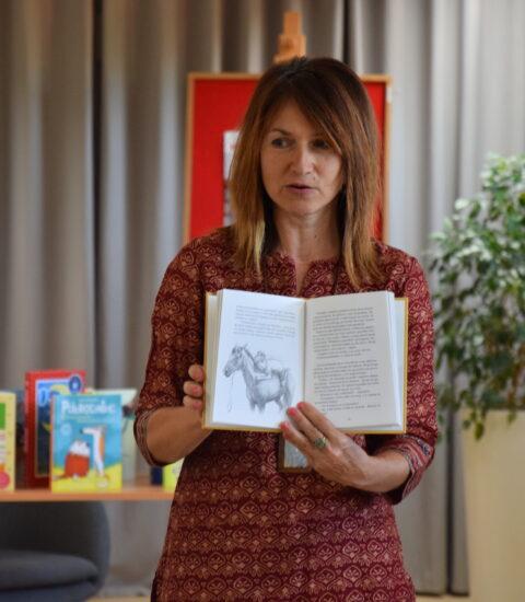 kobieta z otwartą książką stoi przodem