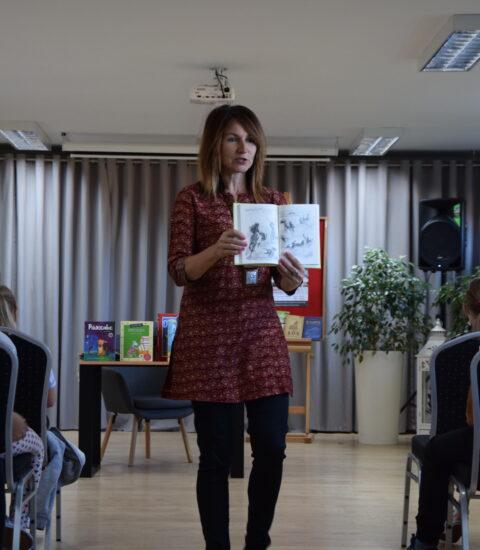 kobieta stoi na środku sali z książką w rękach