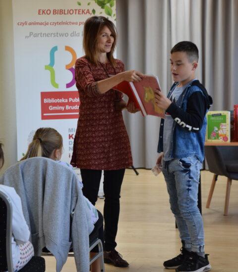 kobieta trzyma książkę obok stoi chłopiec