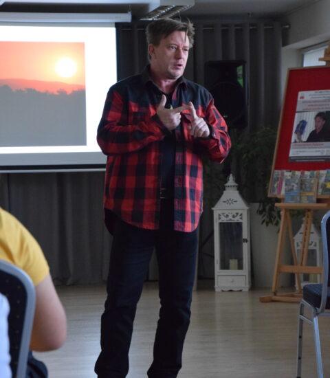 mężczyzna ubrany w koszulą w kratę stoi pomiędzy rzędami krzeseł