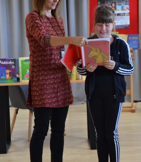 kobieta trzyma książkę obok stoi dziewczynka