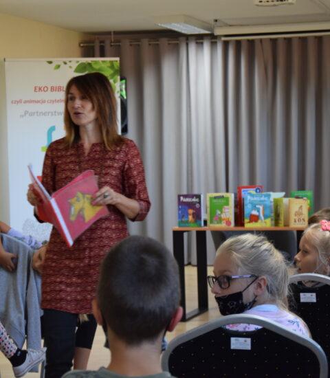 kobieta z książką w rękach chodzi między publicznością