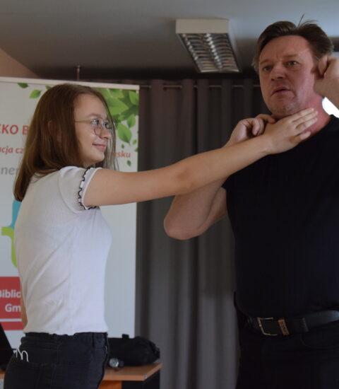 mężczyzna ubrany na czarno stoi obok dziewczyny, demonstruje chwyty samoobrony