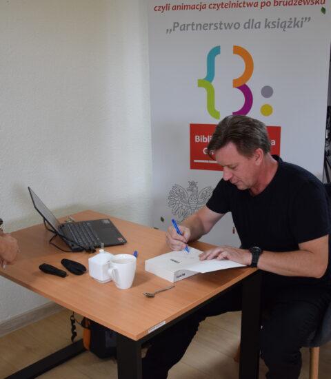 mężczyzna ubrany na czarno siedzi przy stole, podpisuje książkę