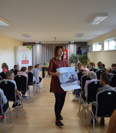 kobieta z planszą przedstawiającą ilustrację w rękach chodzi między, skierowana do publiczności