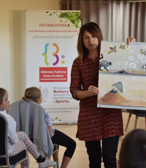 kobieta pokazuje planszę przedstawiającą ilustrację