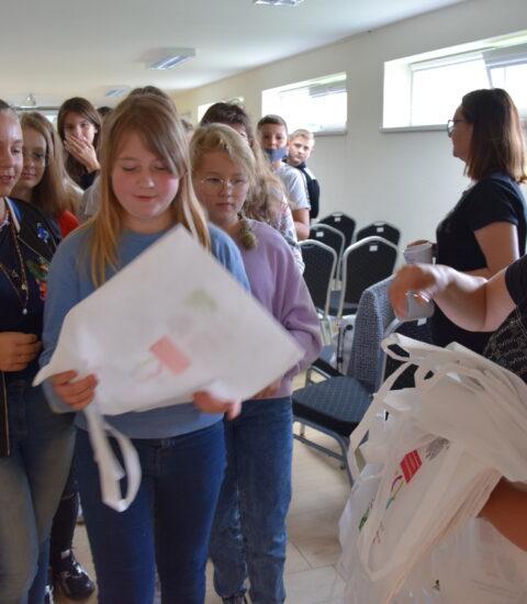 grupa młodzieży wychodzi z sali, kobieta wręcza białe torby