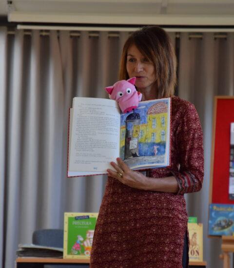 kobieta z otwartą książką, na prawej ręce maskotka świnka
