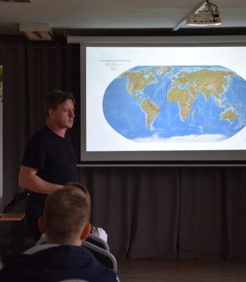 mężczyzna ubrany na czarno stoi przed publicznością, w tle ekran z mapą świata