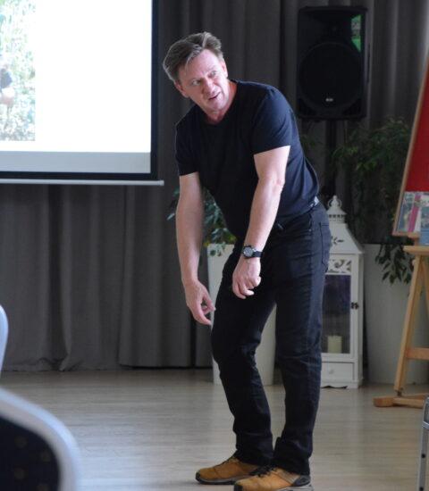 mężczyzna ubrany na czarno stoi przed publicznością, pochyla się do podłogi