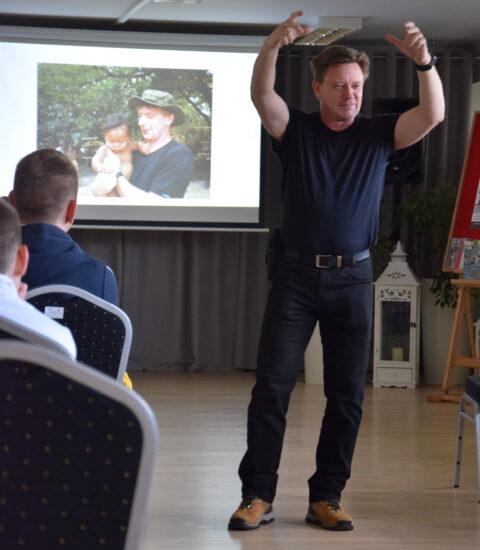mężczyzna ubrany na czarno stoi przed publicznością, ma uniesione obie ręce