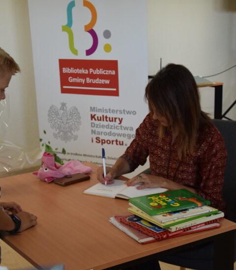 kobieta siedzi przy stole, podpisuje książkę, przed nią stoi chłopiec