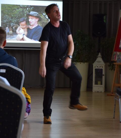 mężczyzna ubrany na czarno stoi przed publicznością, ma podniesioną lewą nogę