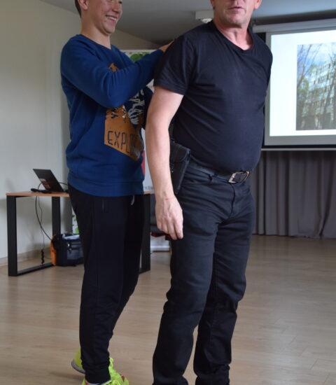 mężczyzna ubrany na czarno stoi obok chłopaka, demonstruje chwyty samoobrony