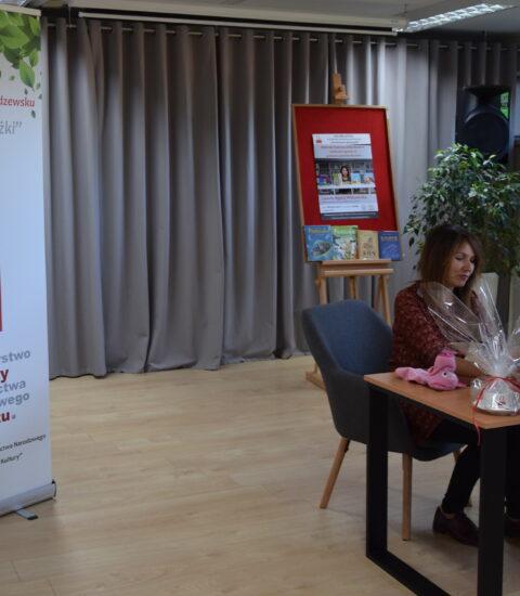 kobieta siedzi przy stole, podpisuje książkę