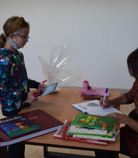 kobieta siedzi przy stole, podpisuje książkę, przed nią stoi dziewczynka