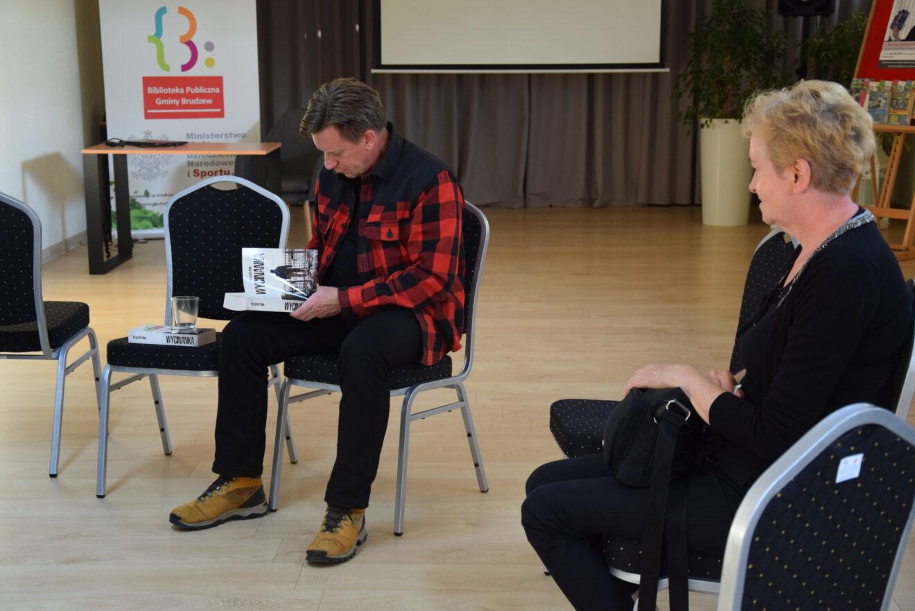 kobieta ubrana na czarno siedzi naprzeciw mężczyzny podpisującego książkę