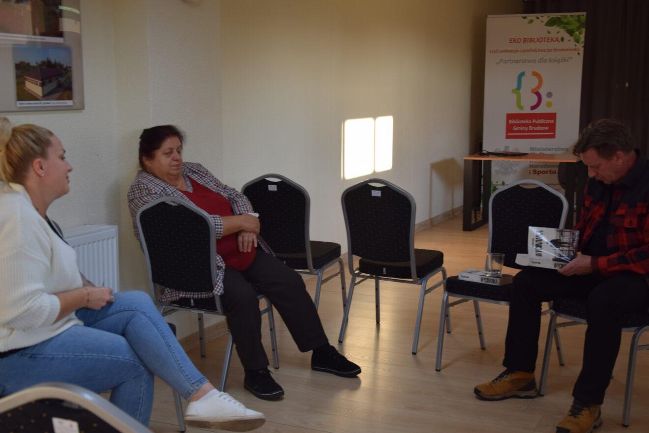 dwie kobiety siedzące naprzeciw mężczyzny podpisującego książkę
