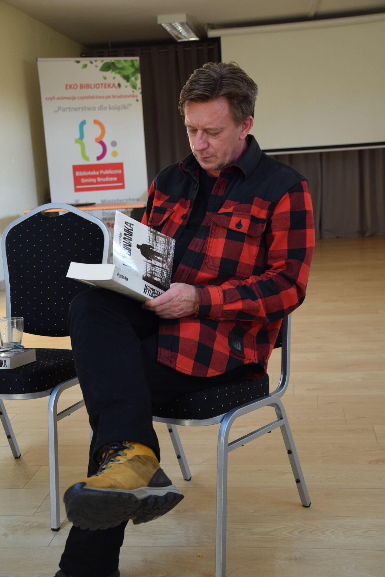 mężczyzny siedzi na krześle, podpisuje książkę