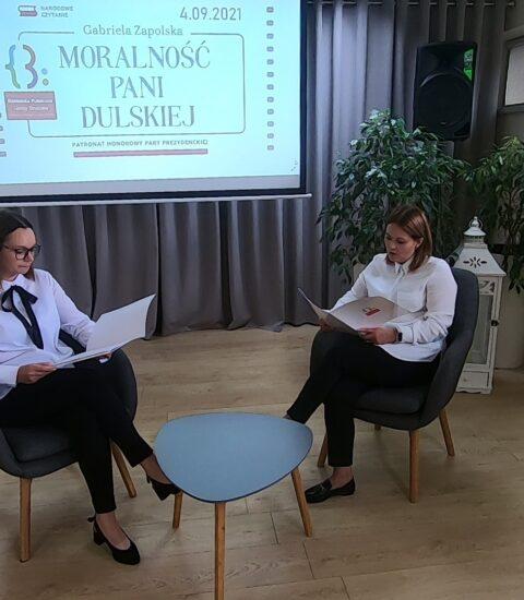 dwie kobiety siedzące naprzeciw siebie, czytają