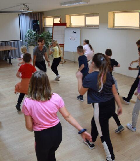 grupa dzieci tańcząca, przed nimi dorosła kobieta