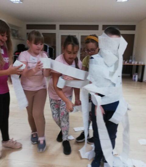 cztery dziewczynki, owijają chłopca papierem toaletowym