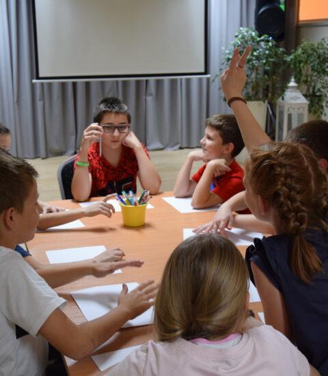 grupa dzieci siedzi przy stole, przed sobą mają białe kartki
