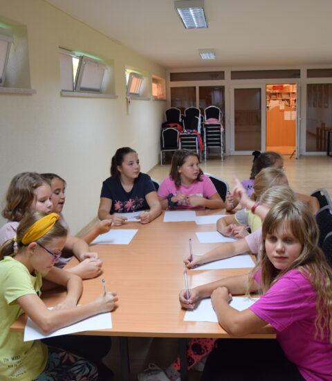 dziewięć dziewczynek siedzi przy stole, piszą na kartkach