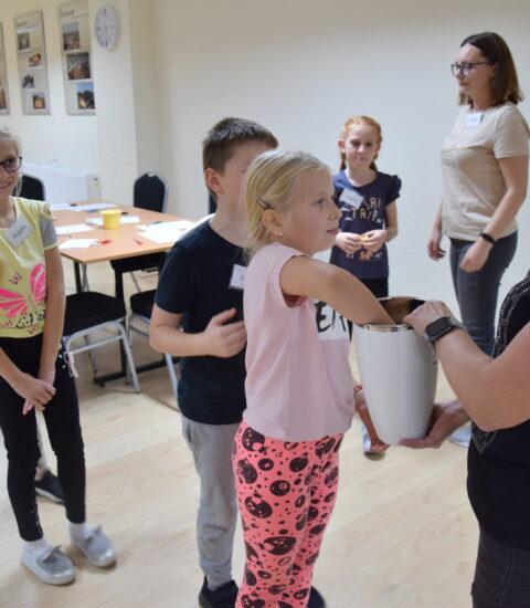 dzieci ustawione w kolejce, dziewczynka losuje coś z białego wazonu, który trzyma dorosła kobieta