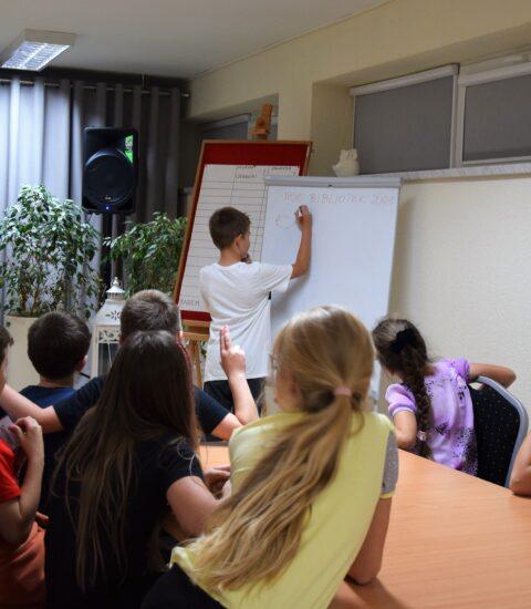 chłopiec rysuje na tablicy, kilkoro dzieci siedzących przy stole patrzy w jego stronę