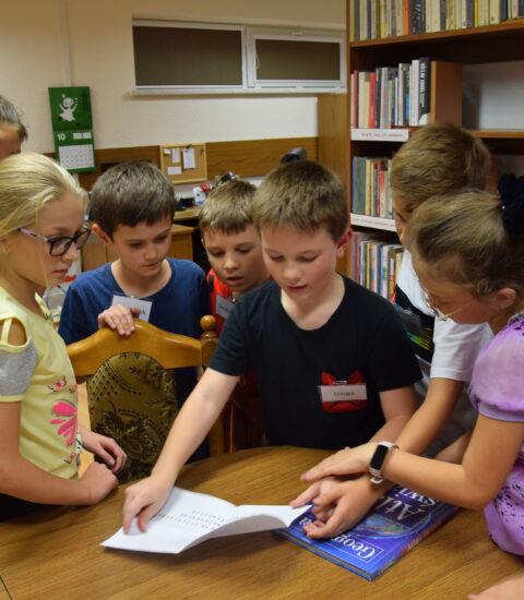 grupa dzieci pochylona nad stołem, rozwiązują zagadkę