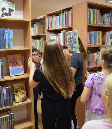 kilkoro dzieci chodzi między regałami bibliotecznymi
